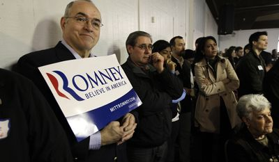 Steve Bailey, of Vets for Romney, shows his support for Republican presidential candidate, former Massachusetts Gov. Mitt Romney, has he and others listen to a speech being given by Republican presidential candidate Rep. Ron Paul, R-Texas, during a Washington state caucus meeting, Saturday, March, 3, 2012, in Puyallup, Wash. (AP Photo/Ted S. Warren)