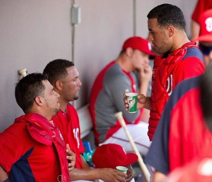 Nationals catcher Jhonatan Solano (left) shares strategy with catcher Sandy Leon (right) during an exhibition Friday at Space Coast Stadium in Viera, Fla. Both are behind Wilson Ramos and Jesus Flores on Washington's depth chart. (Andrew Harnik/The Washington Times)