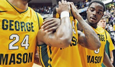 George Mason guard Andre Cornelius covers his face as he leaves the court with teammates Ryan Pearson (24) and Jonathan Arledge after losing to VCU in the CAA semifinals. GMU, which trailed 22-0, lost 74-64. (Associated Press)