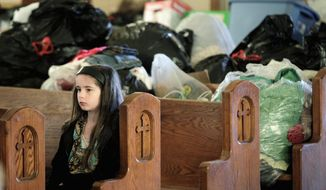 A girl attending mass at St. Francis Xavier Catholic Church sits in a pew in front of clothing and supplies that have been collected to aid victims of a tornado in Henryville, Ind., Sunday, March 4, 2012. The church was in the path of a tornado that destroyed much of the town. Three people were killed in Southern Indiana by Tornados on Friday. (AP Photo/Michael Conroy)