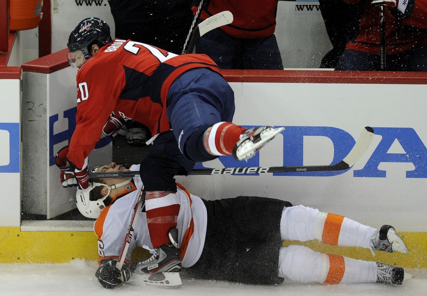 Washington Capitals left wing Troy Brouwer (20) collides with Philadelphia Flyers defenseman Erik Gustafsson, bottom, during the first period of an NHL hockey game, Sunday, March 4, 2012, in Washington. (AP Photo/Nick Wass)