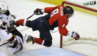 Washington Capitals' Alex Ovechkin (8) leaps through the air after a shot on goal stopped by New Jersey Devils' goalie Johan Hedberg (1) during the second period of an NHL game, Friday, March 2, 2012, in Washington. New Jersey defeated Washington 5-0. (AP Photo/Richard Lipski)