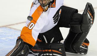 Philadelphia Flyers goalie Ilya Bryzgalov (30) reaches for the puck against the Washington Capitals during the third period of an NHL game, Sunday, March 4, 2012, in Washington. The Flyers won 1-0. (AP Photo/Nick Wass)