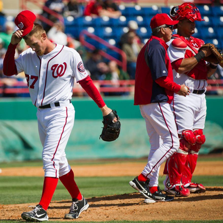 Washington Nationals starting pitcher Stephen Strasburg (37) is pulled by Washington Nationals manager Davey Johnson, second from right, at the top of the third inning during a spring training game against the Astros at Space Coast Stadium, Viera, Fla., Sunday, March 4, 2012. The Nationals lost 10-2. Also pictured is Washington Nationals catcher Wilson Ramos, right. (Andrew Harnik/The Washington Times)