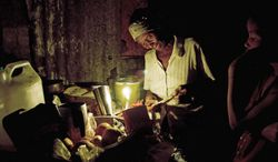 A Haitian woman cooks by candlelight in Port-au-Prince, Haiti. Only a quarter of Haitians have regular access to electricity, and the scarcity touches just about every aspect of Haitian life. (Associated Press)