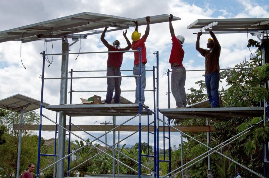 Technicians install solar panels to supply power to a health center and a fish hatchery in Boucan Carre, Haiti. The panels will also provide the town with dependable electricity for the first time. (Associated Press)