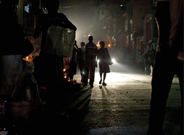 People make their way down a dark street in Port-au-Prince, Haiti, recently. Haitian President Michel Martelly's administration hopes to double the number of rural homes with access to power by helping villagers acquire solar-power systems. (Associated Press)