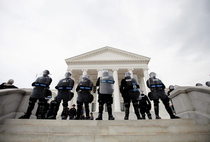 Virginia State Police stand by as protesters are removed from the front steps of the state Capitol in Richmond on Saturday. (Associated Press)