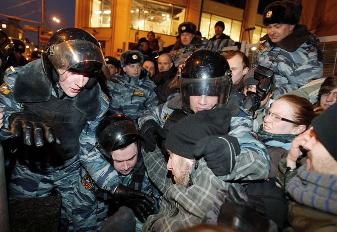 Russian police subdue demonstrators who refused to disperse in Moscow on Monday. Protesters contested the outcome of the Russian presidential election, pointing to reports of widespread violations in balloting. (Associated Press)