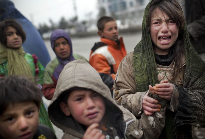An Afghan refugee girl reacts March 4, 2012, after another child stole her food voucher while she was queuing in front a truck organized by the World Food Program in Kabul, Afghanistan. (Associated Press)