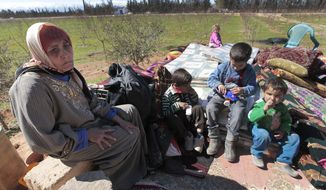 Hassana Abu Firasl (left), a Syrian who fled the town of Qusair, near Homs, Syria, is seen with her family at the Lebanese-Syrian border village of Qaa, in eastern Lebanon, on Monday, March 5, 2012. (AP Photo/Hussein Malla)