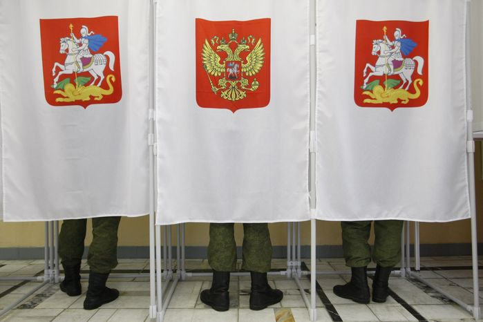 Russian soldiers vote in the nation's presidential election at a polling station in Moscow on Sunday, Ma