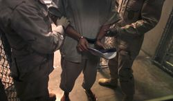 """** FILE ** A handcuffed detainee carries a workbook as he is escorted by guards after attending a """"life skills"""" class in the high-security detention facility on Guantanamo Bay Naval Base in Cuba in March 2010. (AP Photo/Brennan Linsley, File)"""