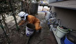 **FILE** A worker scoops up a layer of radiation-contaminated soil and ice in the garden of a private home in Fukushima, Japan, on Feb. 21, 2012. (Associated Press)