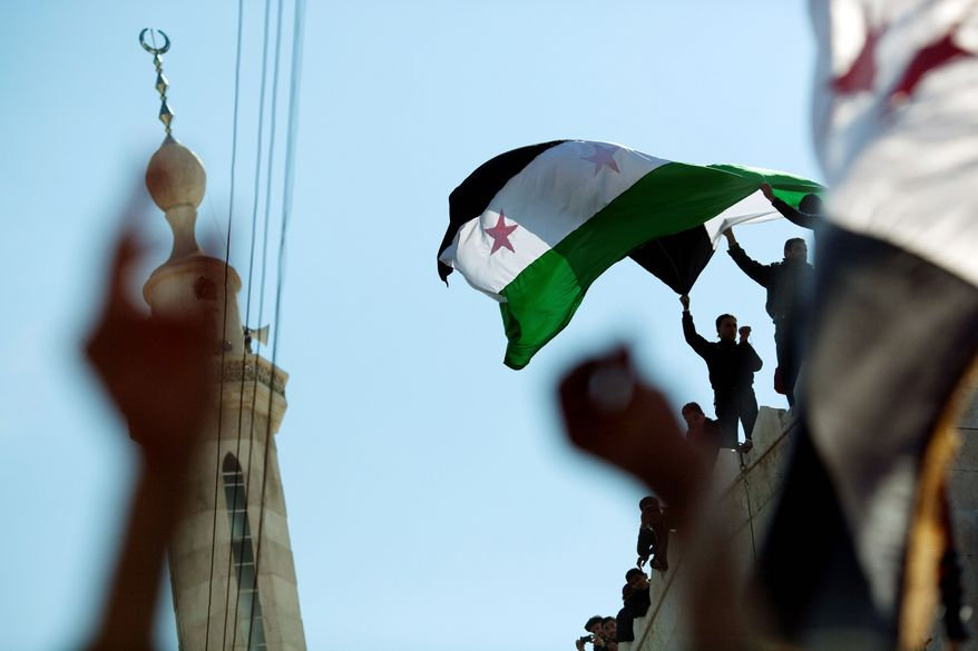 Protesters wave a revolutionary flag on top of a mosque in northern Syria. Regime change in Damascus could break powerful ties with Iran and change the course of defense and foreign policies throughout the Middle East. (Associated Press)