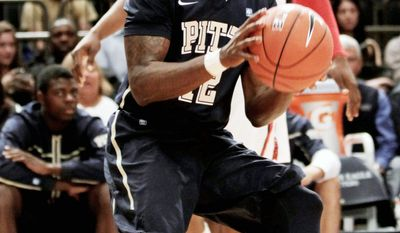 ASSOCIATED PRESS Pittsburgh's Ashton Gibbs looks to shoot while St. John's God'sgift Achiuwa watches. Gibbs scored 20 points in the Panthers' 73-59 Big East tournament victory.