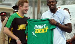 Britain's Prince Harry, left, receives a T-shirt as a gift from Olympic sprint champion Usain Bolt after participating in a mock a mock race in Kingston, Jamaica, Tuesday March 6, 2012. The Prince is in Jamaica as part of the Diamond Jubilee tour in honor of Queen Elizabeth II who celebrates 60 years on the throne. (AP Photo/Collin Reid)