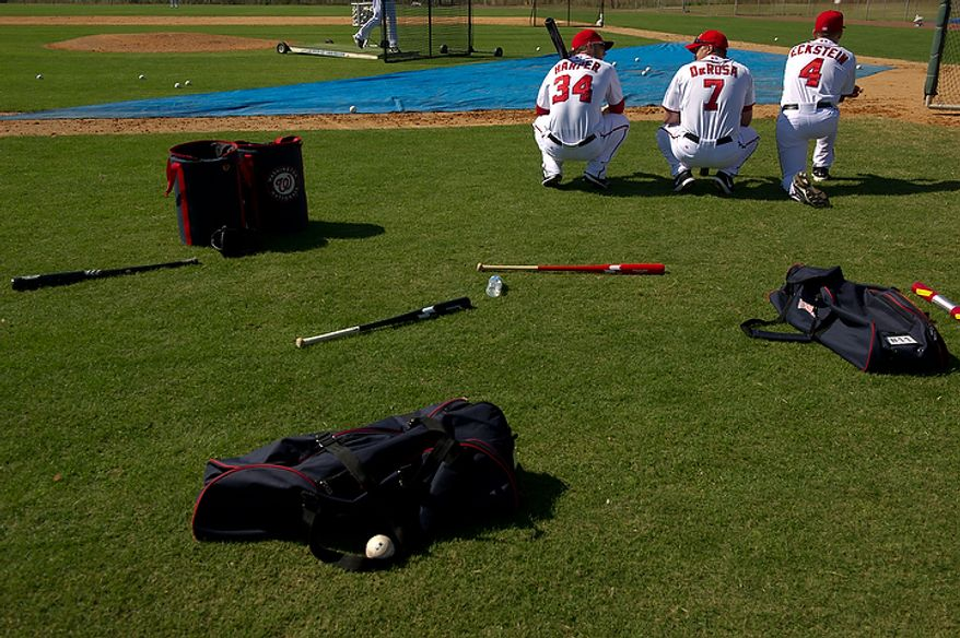 Washington Nationals right fielder Bryce Harper (34) and Washington Nationals infielder Mark DeRosa (7) wait their turn for batting practice next to hitting coach Rick Eckstein (4) during spring training, Viera, Fla., Tuesday, February 28, 2012. (Andrew Harnik/The Washington Times)