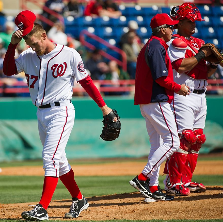 Washington Nationals starting pitcher Stephen Strasburg (37) is pulled by Washington Nationals manager Davey Johnson (5), second from right, at the top of the third inning during a spring training game against the Astros at Space Coast Stadium, Viera, Fla., Sunday, March 4, 2012. The Nationals lost to the Asros 10-2. Also pictured is Washington Nationals catcher Wilson Ramos (3), right. (Andrew Harnik/The Washington Times)