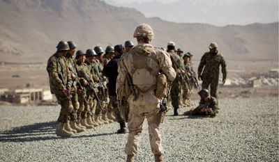 A Canadian Army soldier, mentoring the Afghan National Army, follows a training session of Afghan National Army soldiers at the Kabul Military Training Center on the outskirts of Kabul on Wednesday. The Afghan National Army will be tasked with providing security throughout Afghanistan after the last international troops pull out in 2014. (Associated Press)