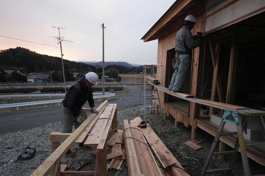 **FILE** Workers build temporary housing for tsunami and radiation evacuees in Hirono, just outside the 20-kilometer (12-mile) nuclear exclusion zone around the Fukushima Dai-ichi nuclear plant in northeast Japan, on Feb. 20, 2012. (Associated Press)
