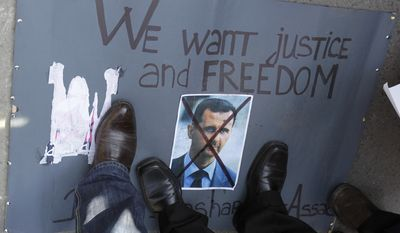 Protesters stand March 6, 2012, on a crossed picture of Syrian President Bashar Assad during a rally against his regime in front of the Syrian embassy in Belgrade, Serbia. (Associated Press)