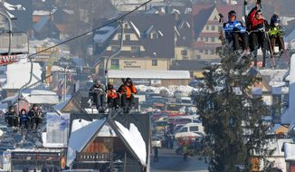 Skiers sit on a chairlift ascending the Kotelnica Mountain in the village of Bialka Tatrzanska, southern Poland. (Associated Press)