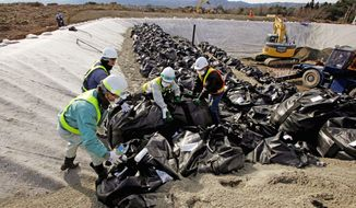 "Workers dump bags filled with radiation contaminated soil - and sometimes the snow that had covered it - from a neighborhood in Hirono. ""We often encounter situations that are not in the manual and wonder if we are doing the right thing,"" worker Takahiro Watanabe said."