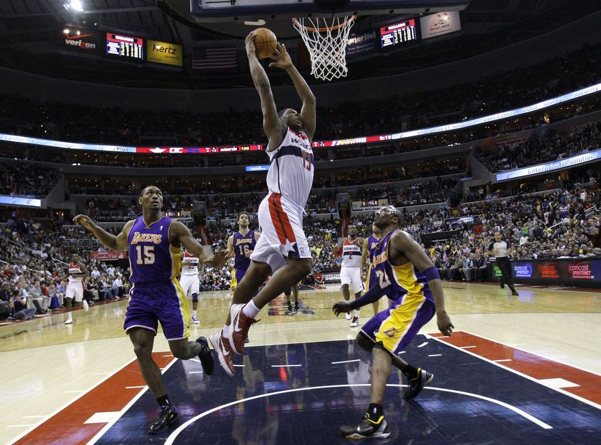 Washington Wizards forward Kevin Seraphin (13) dunks the ball to score against Los Angeles Lakers forward Metta World Peace (15) and guard Kobe Bryant (24) in the fourth quarter at Verizon Center in Washington, Wednesday, March 7, 2012. The Wizards won 106-101. (AP Photo/Jacquelyn Martin)