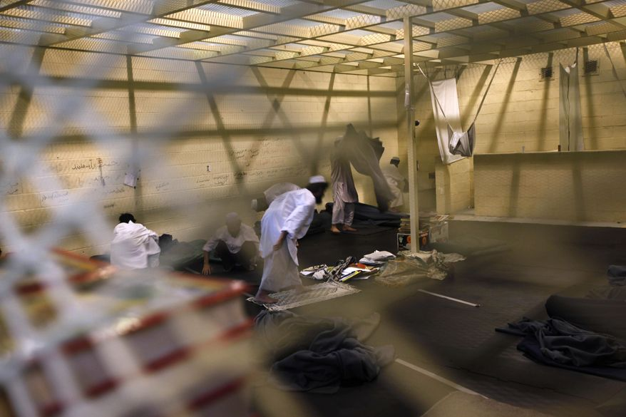 **FILE** Afghan detainees, seen through a mesh wire fence, prepare for noon prayers on March 23, 2011, inside the Parwan detention facility near Bagram Air Field in Afghanistan. (Associated Press)