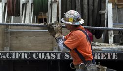 An ironworker with Local Union 416 carries steel rods for a retaining wall at a construction site in Los Angeles on March 6, 2012. (Associated Press)