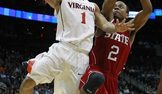 Virginia guard Jontel Evans heads to the hoop as North Carolina State guard Lorenzo Brown defends during the second half in the quarterfinals of the Atlantic Coast Conference tournament, Friday, March 9, 2012, in Atlanta. (AP Photo/John Bazemore)