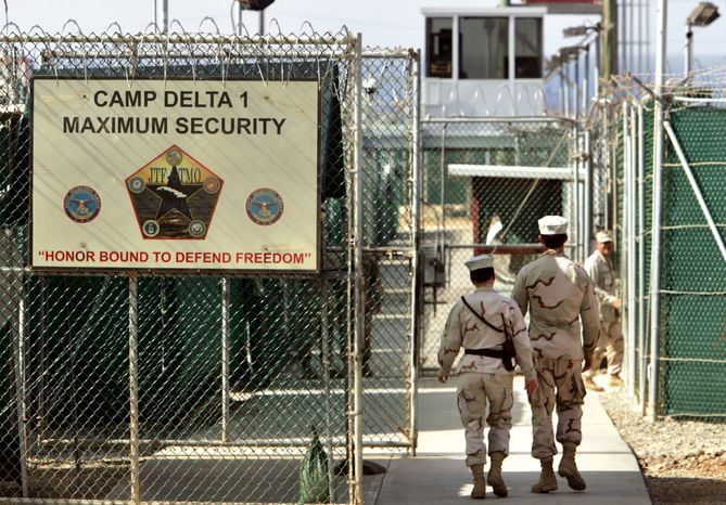 In this June 27, 2006, file photo, reviewed by the U.S. Department of Defense, U.S. military guards walk within the Camp Delta military-run prison at the Guantanamo Bay U.S. Naval Base in Cuba. (AP Photo/Brennan Linsley) ** FILE **