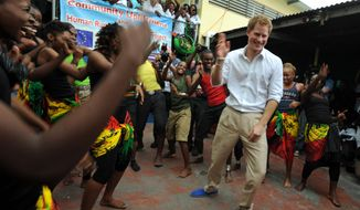 Britain's Prince Harry dances during a visit to Kingston, Jamaica, on Tuesday. Third in line to the throne, the prince is touring the Caribbean as part of a diamond jubilee tour in honor of his grandmother, Queen Elizabeth II, (left). At 85, she still commands respect across her dominions. (Associated Press)