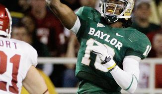 Oklahoma defensive end David King (90) and linebacker Tom Wort (21) give chase as Baylor quarterback Robert Griffin III (10) passes in the first half of an NCAA college football game on Saturday, Nov. 19, 2011, in Waco, Texas. (AP Photo/Tony Gutierrez)