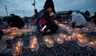 An open area in front of a temporary shopping complex in the devastated city of Kesennuma, Japan, serves as the site of a candlelit memorial to those killed in the earthquake and tsunami on March, 11, 2011. (Associated Press)