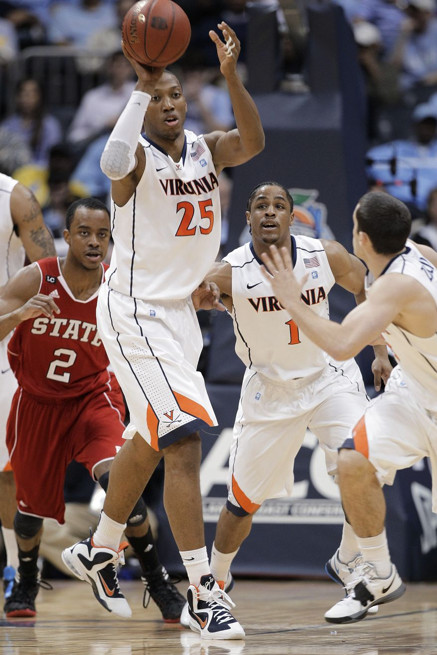 Virginia forward Akil Mitchell passes the ball as North Carolina State guard Lorenzo Brown and Virginia guard Jontel Evans look on durng the first halfin the quarterfinals of the Atlantic Coast Conference men's tournament, Friday, March 9, 2012, in Atlanta. (AP Photo/Chuck Burton)