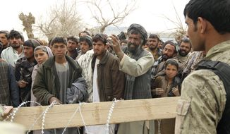 An Afghan soldier speaks to civilians gathered outside a military base in Panjwai, Afghanistan, on Sunday, March 11, 2012, after a U.S. service member allegedly killed 16 Afghans, including nine children and three women. (AP Photo/Allauddin Khan)