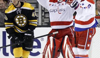 Washington Capitals' Tomas Vokoun and Dennis Wideman celebrate beside Boston Bruins' David Krejci after beating the Bruins 4-3 in Boston, Saturday, March 10, 2012. (AP Photo/Michael Dwyer)