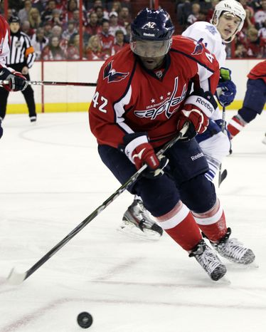Washington Capitals right wing Joel Ward (42) goes for the puck as Toronto Maple Leafs right wing Nikolai Kulemin looks on during the second period on Sunday, March 11, 2012, in Washington. (AP Photo/Carolyn Kaster)