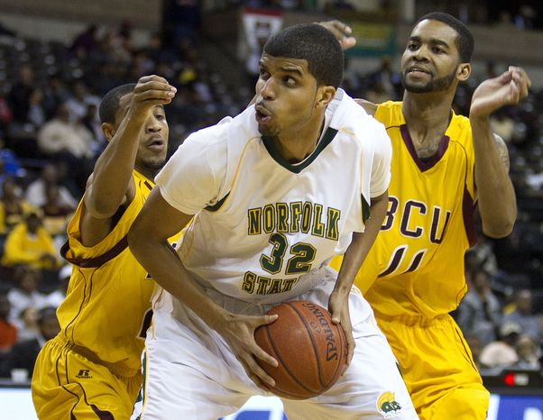 Norfolk State's Marcos Tamares (32) is guarded by Bethune-Cookman Kevin Dukes (21) and Javoris Bryant (11) during the first half of an NCAA college basketball game in the championship of the Mid-Eastern Athletic Conference tournament in Winston-Salem, NC., Saturday, March 10, 2012. (AP Photo/Lynn Hey)