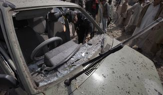 A Pakistani police officer examines a parked car damaged in a suicide bombing in the Badhber area on the outskirts of Peshawar, Pakistan, on Sunday, March 11, 2012. (AP Photo/Mohammad Sajjad)