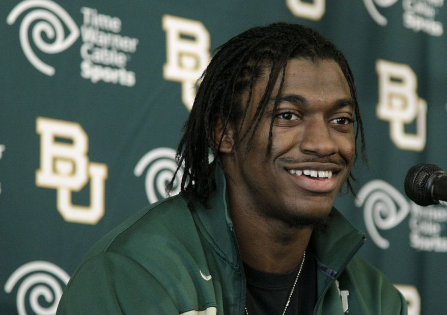 FILE - In this Jan. 11, 2012, file photo, Heisman Trophy winner Robert Griffin III attends a news conference after announcing that he would skip his senior year at Baylor and enter the NFL draft in Waco, Texas. The Washington Redskins have a deal in place to acquire the No. 2 pick from the St. Louis Rams in the NFL draft and plan to take Griffin. (AP Photo/Tony Gutierrez, File)