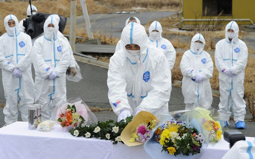Mourners in protective suits and masks gather for prayers for their loved ones who were killed in the last year's earthquake and tsunami,  inside the contaminated exclusion zone near the crippled Fukushima Dai-ichi nuclear power plant, in Okuma, Fukushima prefecture, Japan Sunday, March 11, 2012.(AP Photo/Kyodo News)