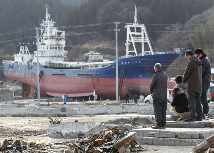 With the back drop of the 330 ton fishing vessel Kyotoku Maru No. 18 which was flung 800 meters (0.5 mile) inland from Kesennuma port by the March 11, 2011, tsunami, the Kikuta family observe a moment of silence at a site where their house once stood at 2:46 PM, the time the earthquake hit one year ago, in Kesennuma, Iwate prefecture, northeastern Japan, Sunday, March 11 2012. T (AP Photo/Koji Sasahara)