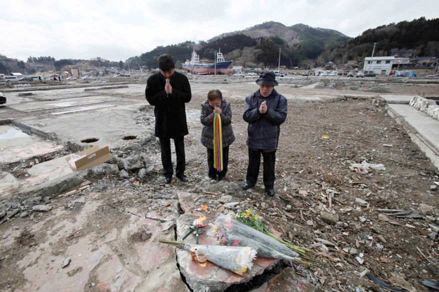 Masayuki Horii, left, accompanied by his father, Tadashi, right, and Megumi Kumagai, center, pray for Masayuki's late wife who was killed by the March 11, 2011, tsunami, in Kesennuma, Iwate prefecture, northeastern Japan, Sunday, March 11 2012.  (AP Photo/Koji Sasahara)