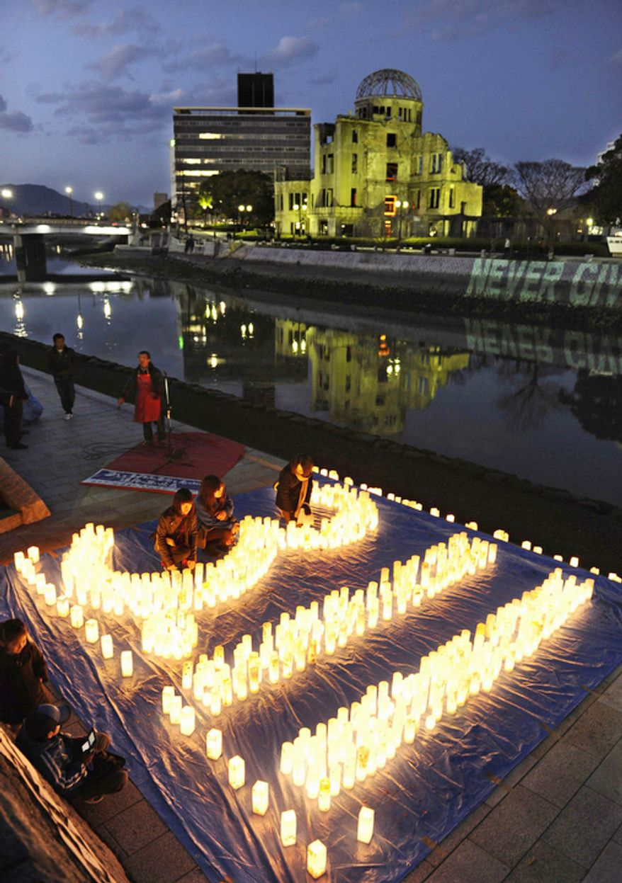 """Candles are lit in the shape of """"3.11 (March 11)"""" as people offer prayer for the victims of the last year's earthquake and tsunami, with a backdrop of the Atomic Bomb Dome in Hiroshima, western Japan Sunday, March 11, 2012.  (AP Photo/Kyodo News)"""
