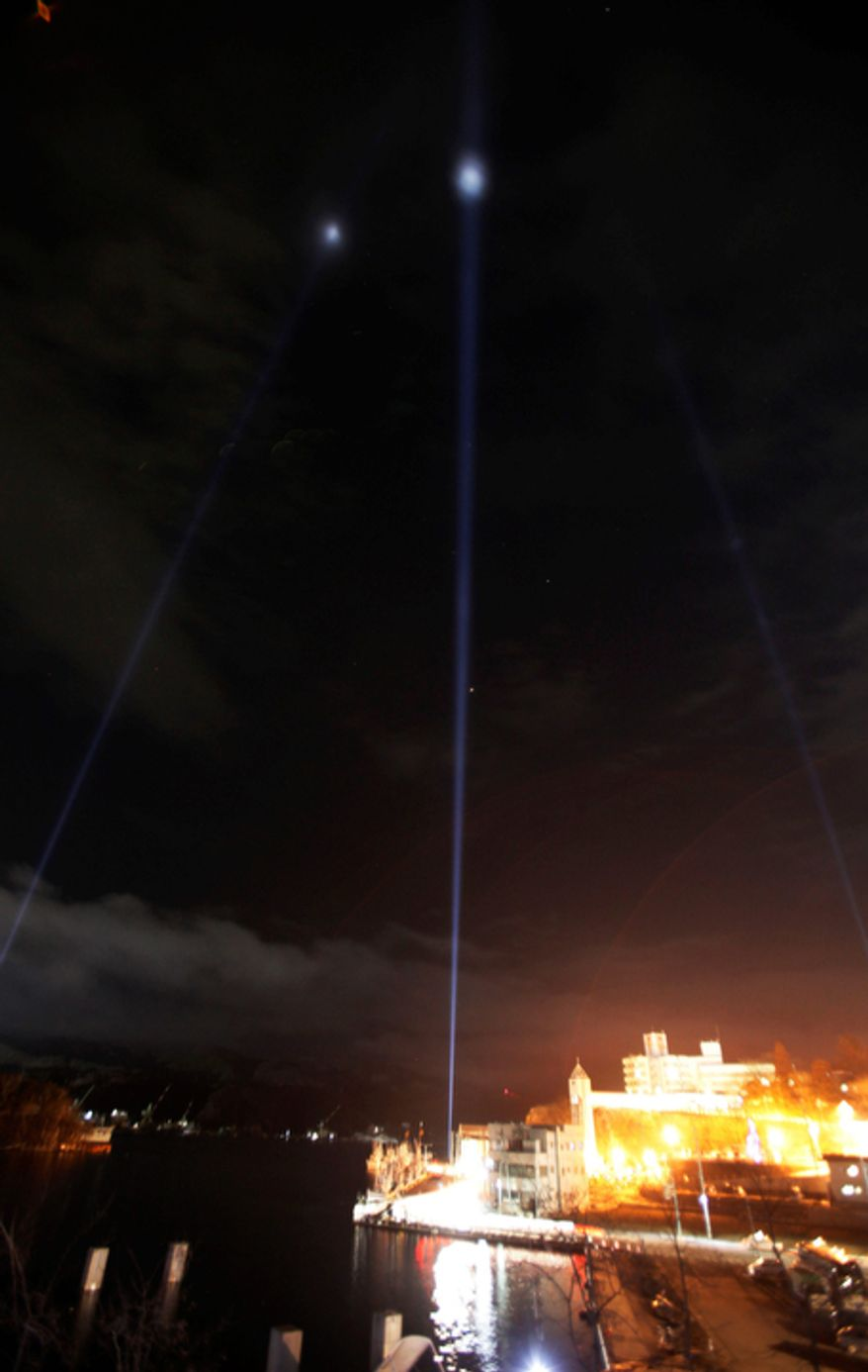 """Three lights are projected in the evening sky during a """"Light from 311 Japan"""" event in the earthquake and tsunami-devastated city of Kesennuma, Iwate Prefecture, northeastern Japan, Sunday, March 11 2012.  (AP Photo/Koji Sasahara)"""