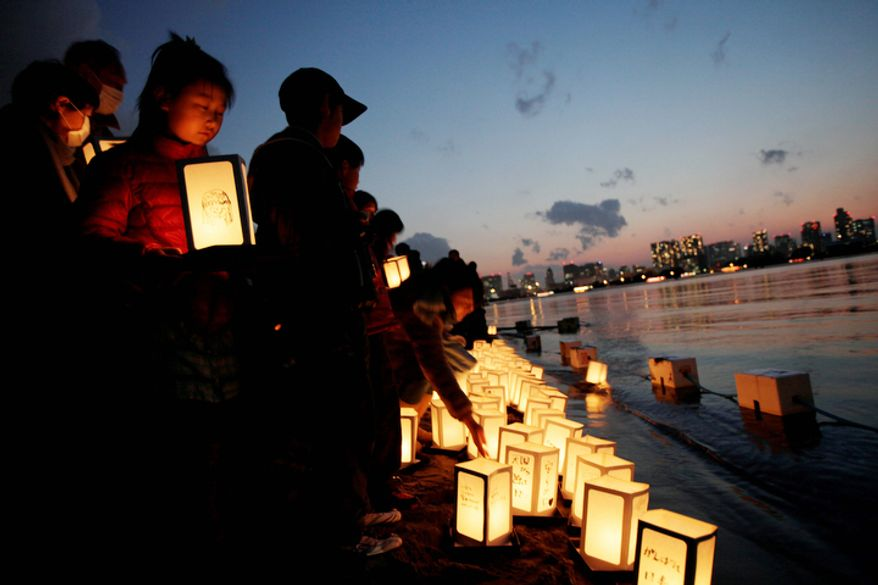 A girl waits her turn to release a lantern into the waters of Tokyo Bay to mark the anniversary of the earthquake and tsunami which devastated northeast Japan, in Tokyo, Sunday, March 11, 2012. (AP Photo/Greg Baker)