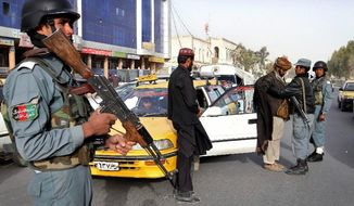 An Afghan policeman stands guard as a partner searches a taxi passenger at a police checkpoint after Sunday's killing of civilians allegedly by a U.S. soldier in Kandahar province, south of Kabul. An Afghan youth recounted Monday a terrifying scene in his home as a lone gunman moved stealthily through it on a killing spree. (Associated Press)